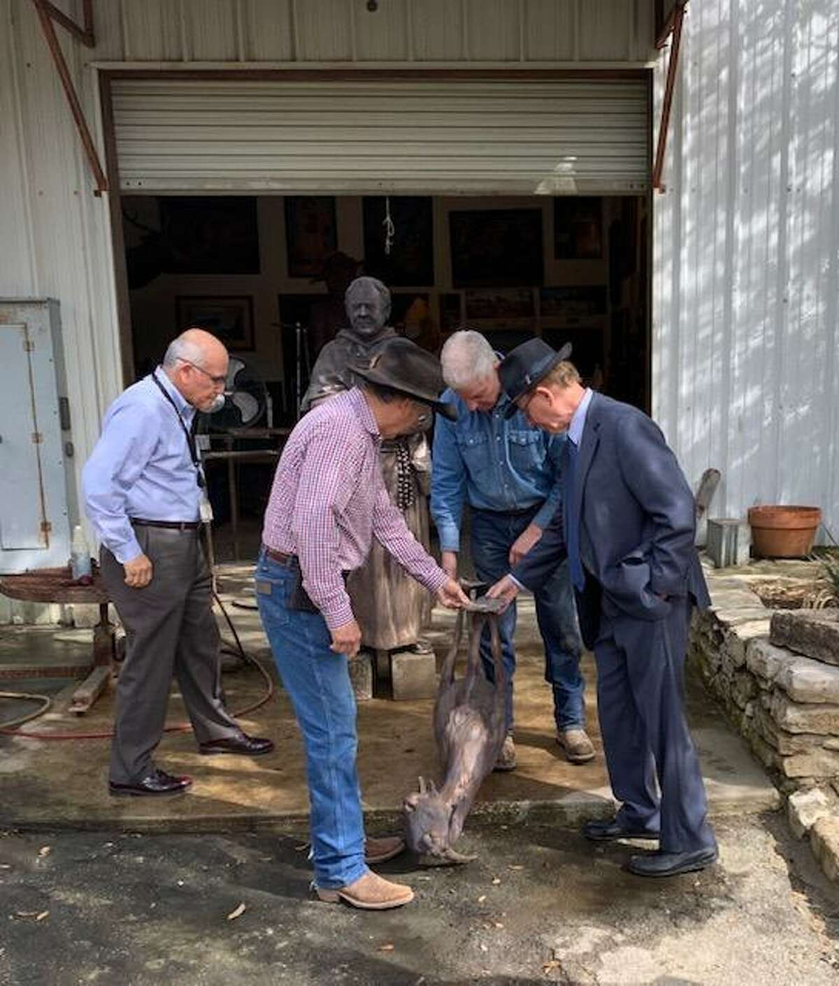 Bexar County Judge Nelson Wolff (right) and Laredo artist Armando Hinojosa examine a bronze sculpture of a goat, with a figure of a Franciscan friar in the background, at Stevens Art Foundry in Bulverde. The pieces crafted by Hinojosa are part of a Founders Monument to be unveiled Saturday in Main Plaza. Also shown are County Architect Oscar Cervantes (left) and Larry Stevens, foundry owner (background).