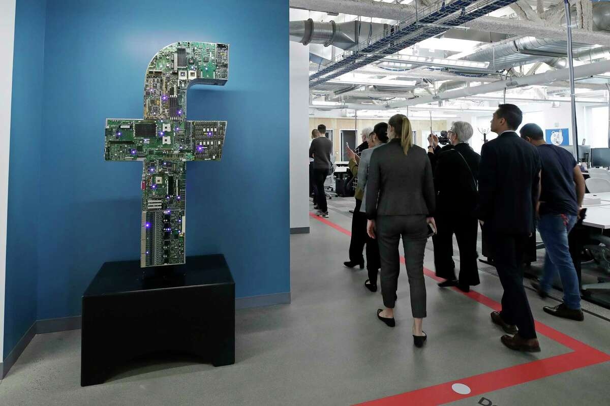 FILE - In this Jan. 9, 2019, file photo, media and guests tour Facebook's new 130,000-square-foot offices, which occupy the top three floors of a 10-story Cambridge, Mass., building. Facebook, which perfected what critics call ?surveillance capitalism,? knows it has serious credibility issues. Those go beyond repeated privacy lapses to include serious abuses by Russian agents, hate groups and disinformation mongers, which Mark Zuckerberg acknowledged only belatedly. (AP Photo/Elise Amendola, File)