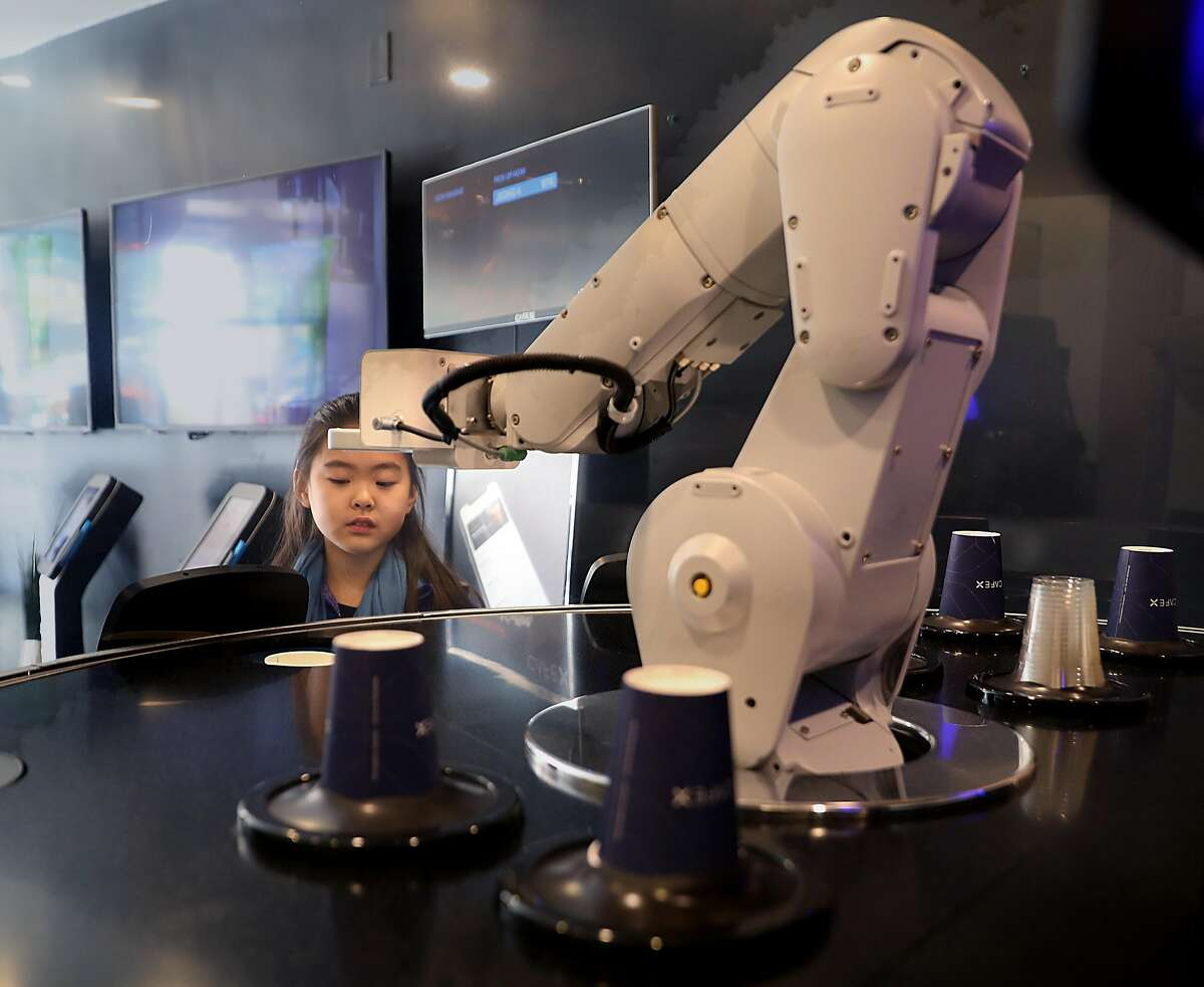 Olivia Jeon, 9 years old, from Toronto watches as robot picks a cup to make a cappuccino for her mother at Cafe X on Market St. on Friday, March 8, 2019, in San Francisco, Calif.