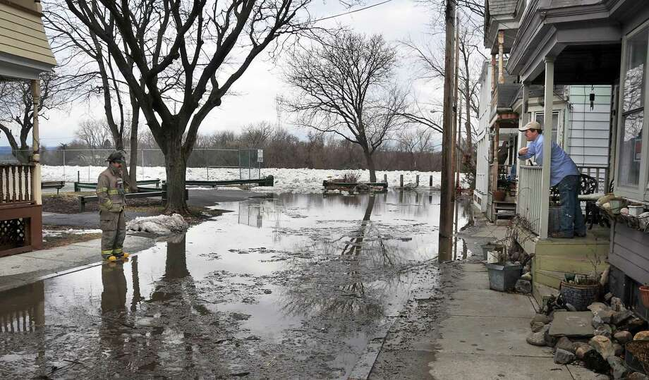 SFD Lt. Timothy Tietz, left, speaks with resident (at right) Eric Laugen as flood waters rise at the north end of Ingersoll Avenue in Schenectady's Stockade district late Tuesday morning January 26, 2010.  (John Carl D'Annibale / Times Union) Photo: John Carl D'Annibale / 00007316A