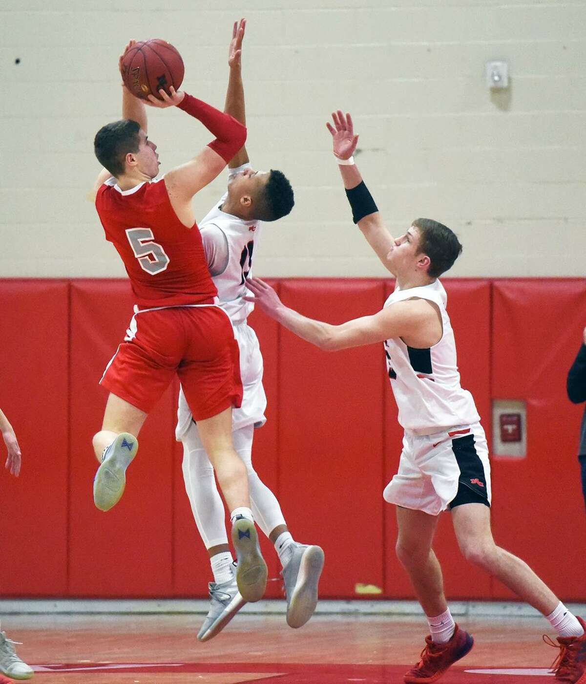 St. Bernard's Max Lee (5) goes up for a shot as New Canaan's Luke Rwambuya and Alex Gibbens defend during a CIAC Division IV quarterfinal game at New Canaan High School on Friday.