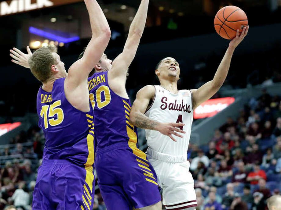 SIUC's Eric McGill (4) heads to the basket past Northern Iowa's Justin Dahl and Spencer Haldeman (30) Friday night in the quarterfinals of the Missouri Valley Conference Tournament in St. Louis. Photo: AP Photo