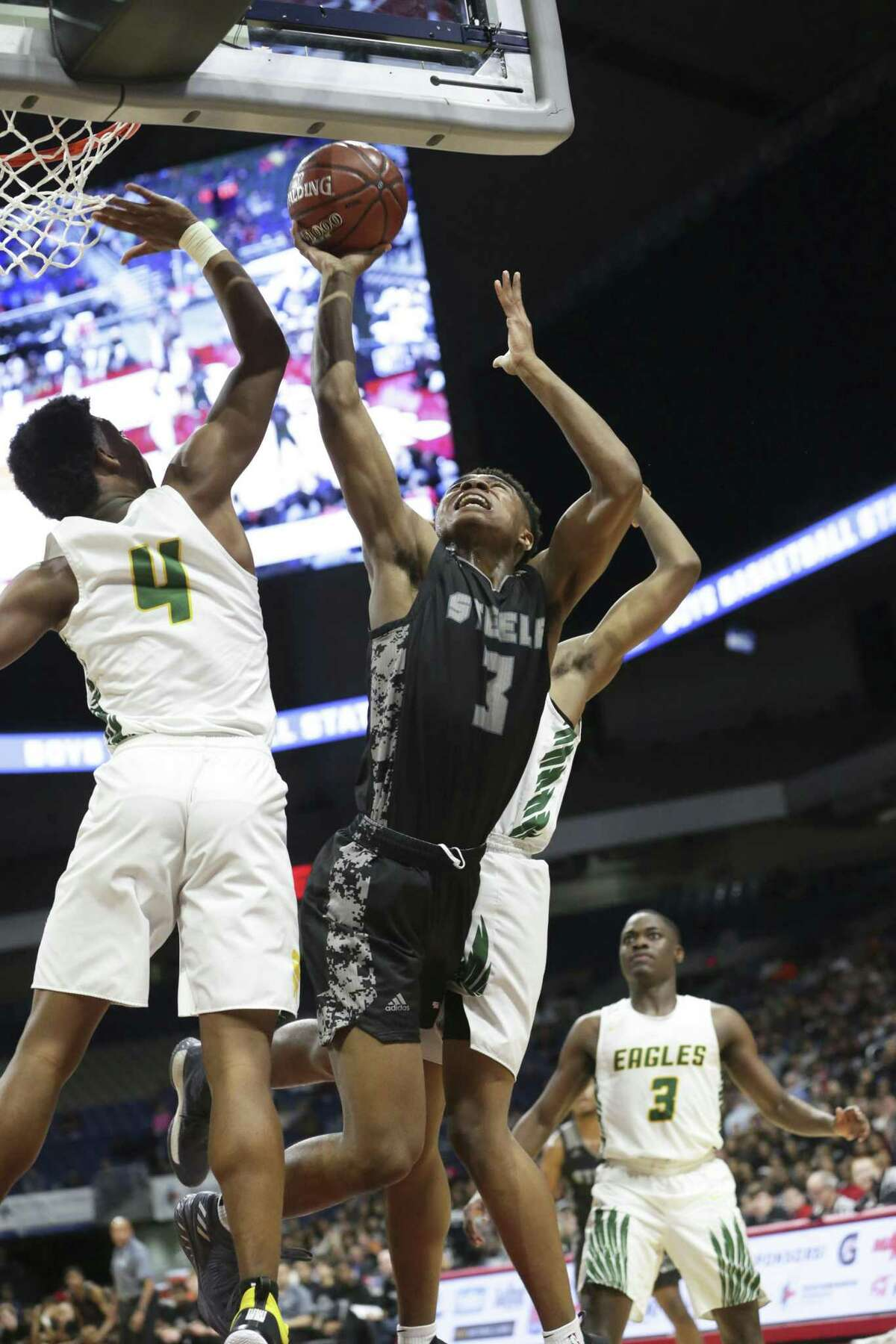 Knight guard Langston Love gets to the glass on Dylan Hamilton as Steele plays Klein Forest in the Class 6A boys state semifinal basketball game at the Alamodome on March 8, 2019.