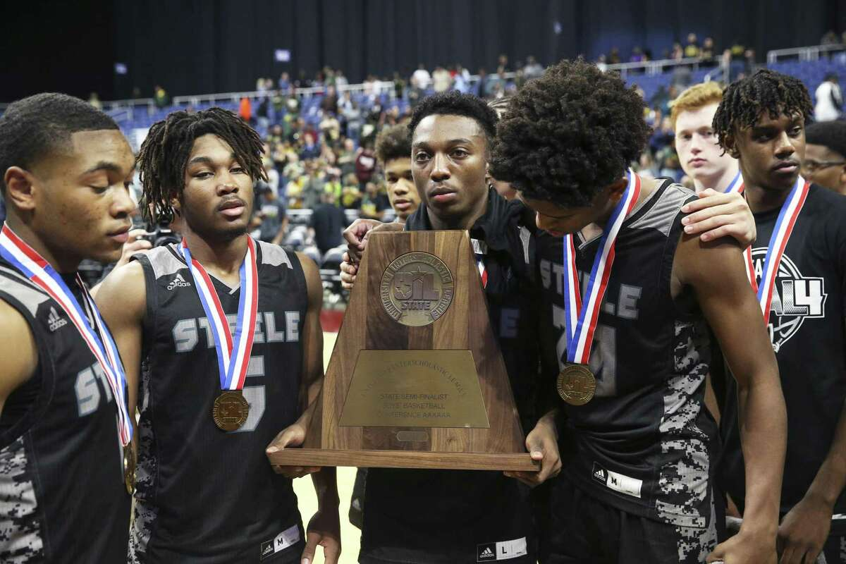 Deject Knight players hold their state semifinalist trophy after losing their first half lead as Steele falls to Klein Forest in the Class 6A boys state semifinal basketball game at the Alamodome on March 8, 2019.