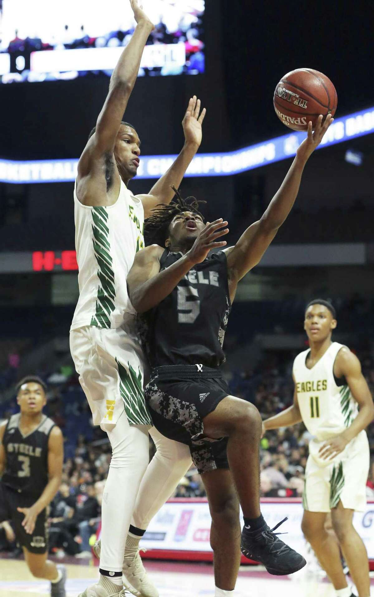 Quincey Sheperd tries a layup against Eagle center Calvin Solomon as Steele plays Klein Forest in the Class 6A boys state semifinal basketball game at the Alamodome on March 8, 2019.