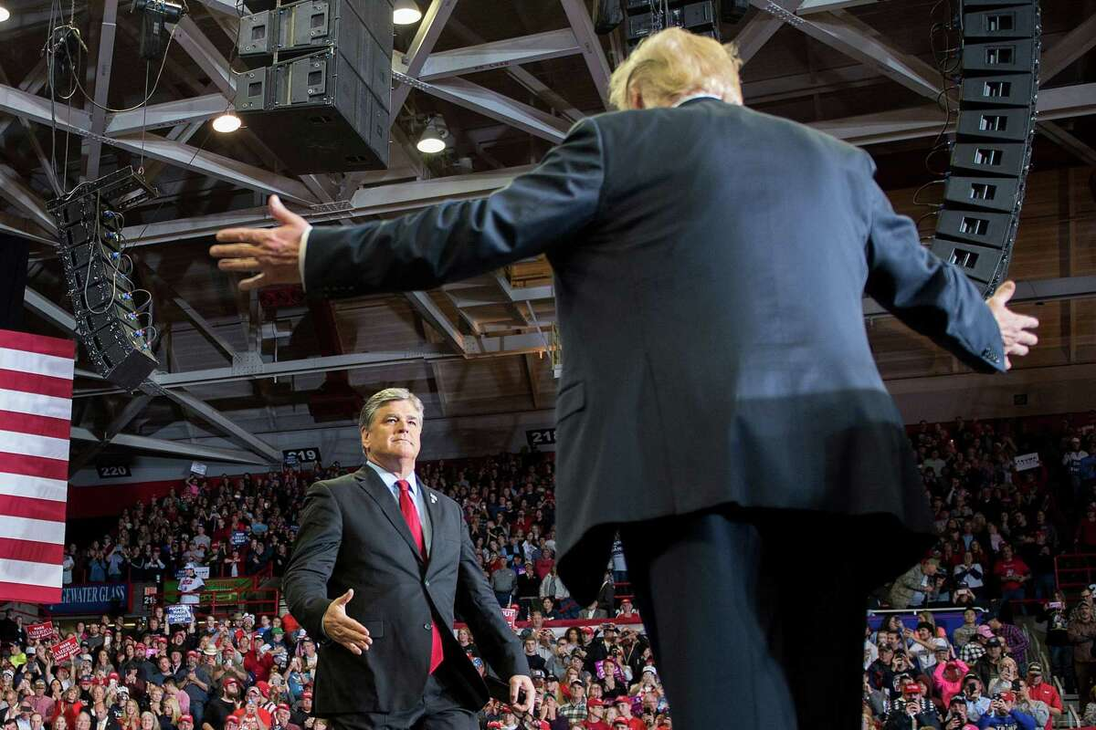 President Donald Trump greets talk show host Sean Hannity at a Make America Great Again rally in Cape Girardeau, Missouri on November 5, 2018.