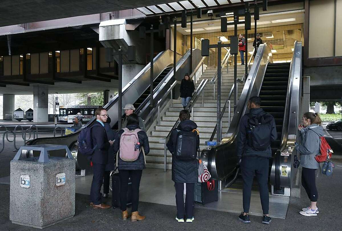 Stranded passengers stand at the entrance to the Rockridge BART station in Oakland, Calif. on Saturday, March 9, 2019 after computer glitches forced a shutdown of the entire transit system.