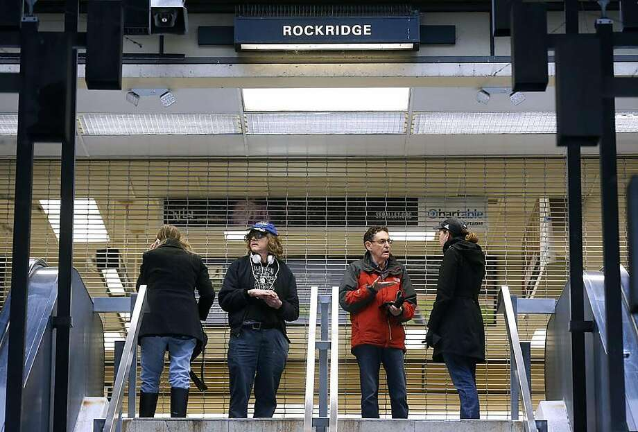 Stranded passengers stand at the entrance to the Rockridge BART station in Oakland, Calif. on Saturday, March 9, 2019 after computer glitches forced a shutdown of the entire transit system. Photo: Paul Chinn / The Chronicle