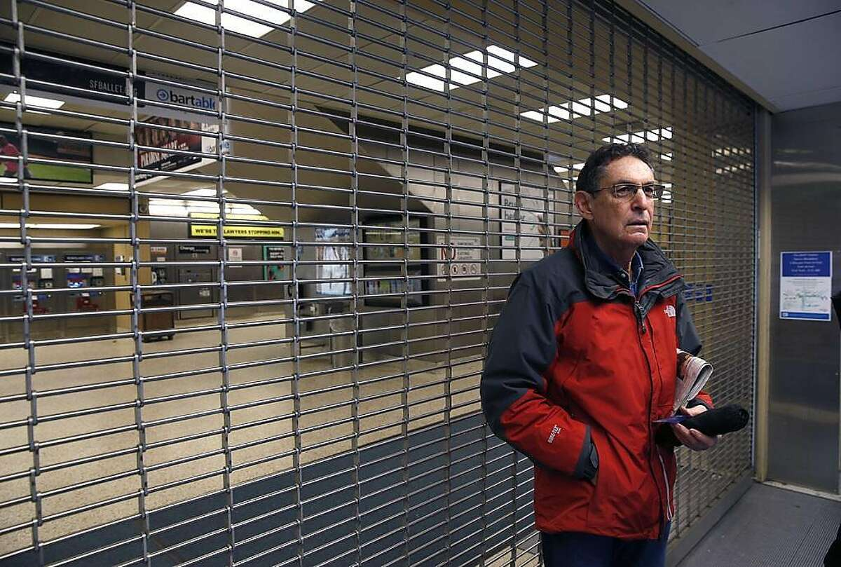 Peter Nussbaum stands in front of the locked the entrance to the Rockridge BART station in Oakland, Calif. on Saturday, March 9, 2019 after computer glitches forced a shutdown of the entire transit system.