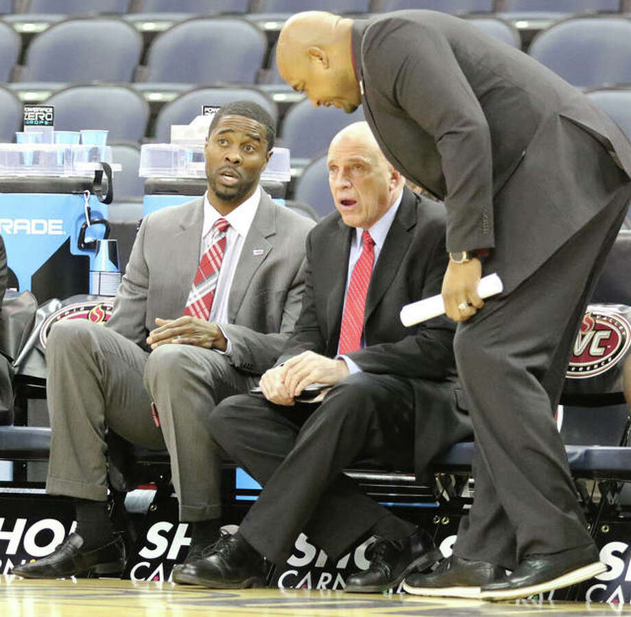 SIUE coach Jon Harris (left) confers with assistants Mike Waldo and Bubba Wells (standing) during Thursday's Ohio Valley Conference Tournament game at Ford Center in Evansville, Indiana. Harris has completed the four years of his four-year contract with SIUE and a decision on his future as Cougars coach is expected soon. Photo: Greg Shashack / The Telegraph