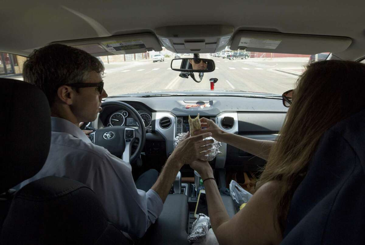 Amy O'Rourke, right, hands over a burrito to her husband, Beto O'Rourke, as they drive roughly 70 miles to the third campaign stop of the day Tuesday, July 31, 2018, in Lubbock, Texas. The O'Rourkes headed to Muleshoe after the town hall at the Cactus Theater.