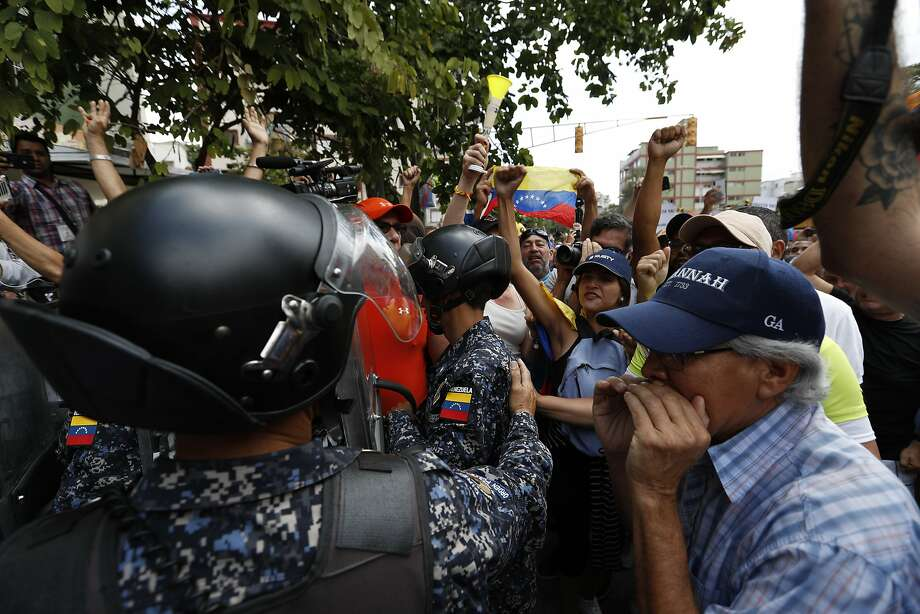 Opposition protesters confront police in Caracas while venting their anger over a blackout and shortages of basic necessities. Photo: Eduardo Verdugo / Associated Press
