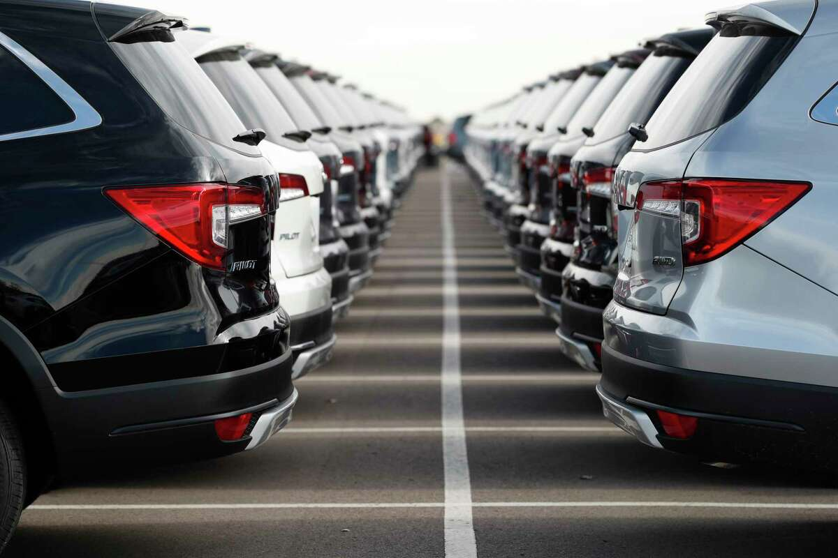 FILE- In this Nov. 28, 2018, file photo a long lines of unsold 2019 Pilot sports-utility vehicles sit at a Honda dealership in Highlands Ranch, Colo. New vehicle prices and interest rates are on the rise, causing millions of people to fall behind on their auto loan payments. But experts say you can avoid being one of them by preparing yourself before you buy and not getting caught up in the emotional moment of going after all the options that you desire. (AP Photo/David Zalubowski, File)