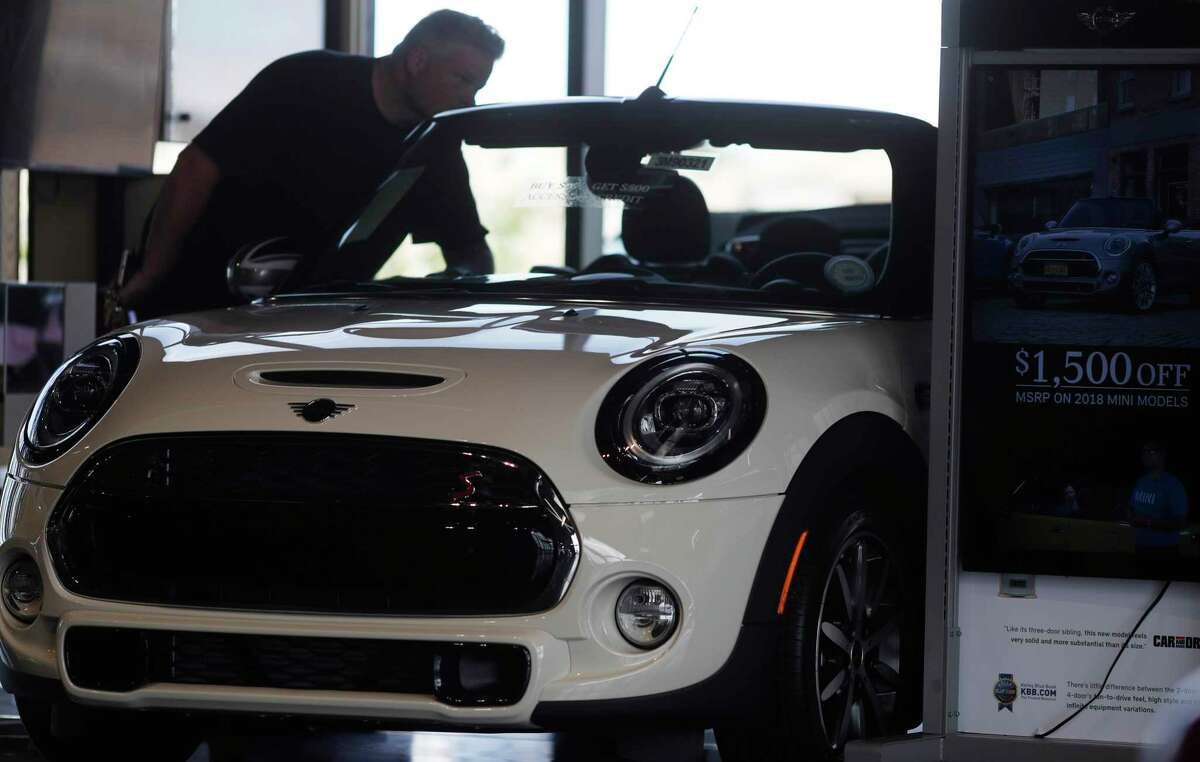 FILE- In this Aug. 30, 2018, file photo, a prospective buyer looks over a 2019 Cooper S convertible on the showroom floor of a Mini dealership in Highlands Ranch, Colo. New vehicle prices and interest rates are on the rise, causing millions of people to fall behind on their auto loan payments. But experts say you can avoid being one of them by preparing yourself before you buy and not getting caught up in the emotional moment of going after all the options that you desire. (AP Photo/David Zalubowski, File)