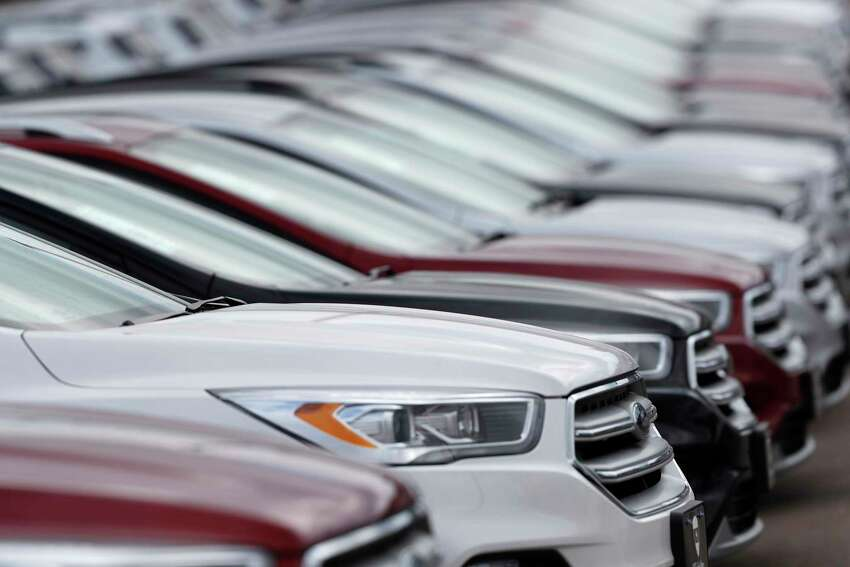 FILE- In this Sunday, Feb. 17, 2019, file photo, unsold 2019 Escape sports-utility vehicles sit in a long row at a Ford dealership in Broomfield, Colo. New vehicle prices and interest rates are on the rise, causing millions of people to fall behind on their auto loan payments. But experts say you can avoid being one of them by preparing yourself before you buy and not getting caught up in the emotional moment of going after all the options that you desire. (AP Photo/David Zalubowski, File)
