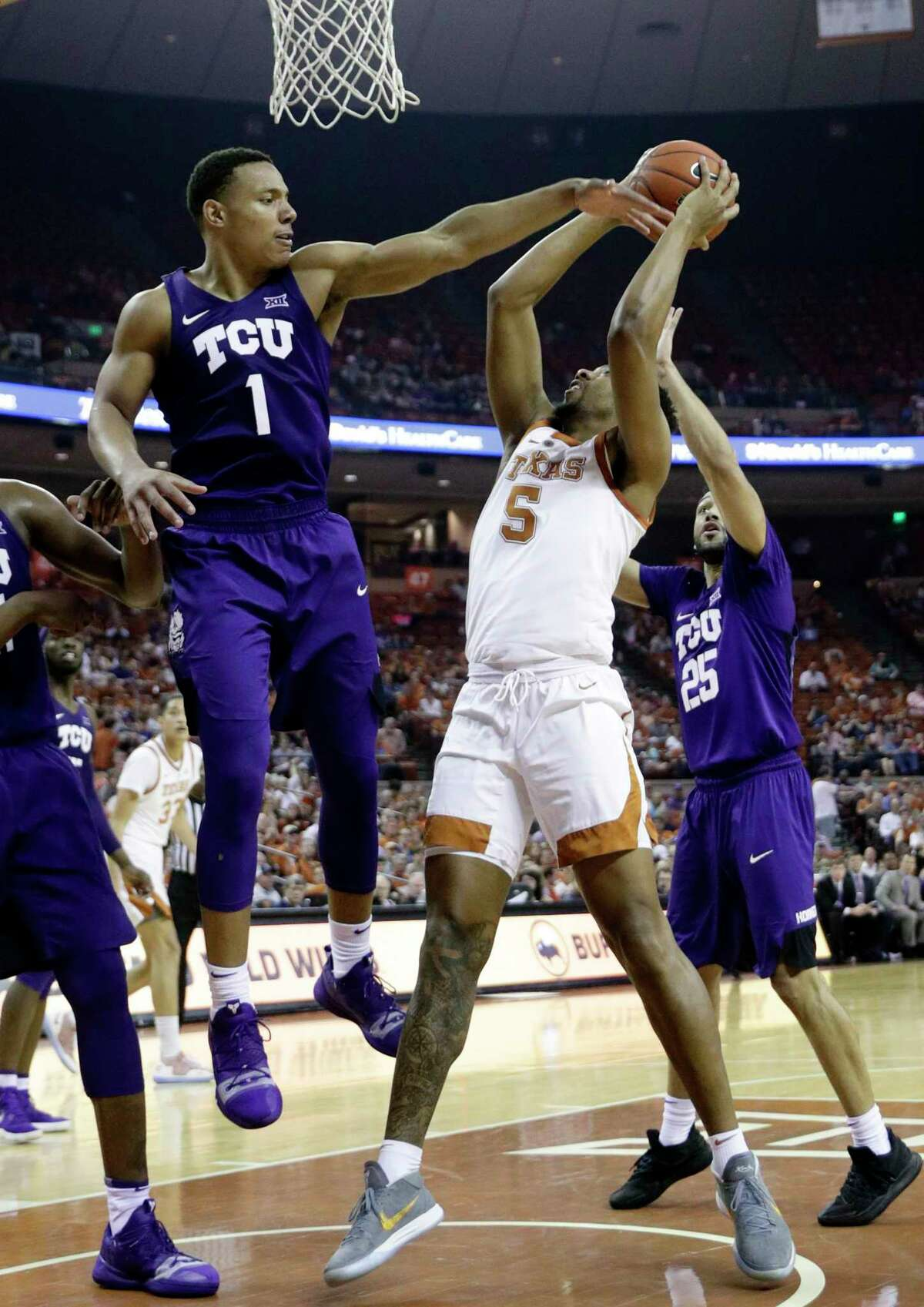Texas forward Royce Hamm Jr. (5) is pressured by TCU guard Desmond Bane (1) and guard Alex Robinson (25) during the second half of an NCAA college basketball game, Saturday, March 9, 2019, in Austin, Texas. (AP Photo/Eric Gay)