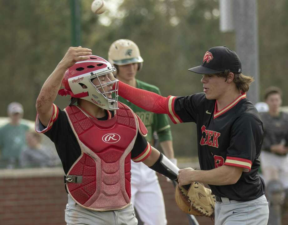 Caney Creek catcher Nick Richards (12) celebrates with Cody Fay (13) after Richards tags a runner out at home plate at the end of the first inning of the second game of a non-district double header Saturday, March 9, 2019 at The Woodlands Christian Academy. Photo: Cody Bahn, Houston Chronicle / Staff Photographer / © 2018 Houston Chronicle