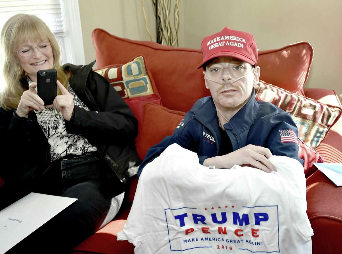 West Haven, Connecticut - Saturday, March 9, 2019: Jay W. Barrett, 44, of West Haven, terminally ill with cystic fibrosis who is a President Donald Trump fan and received a phone call from the President Tuesday right,, with visiting West Haven Mayor Nancy R. Rossi, left, shows of an autographed Make America Great Again hat, an official Donald Trump Presidential campaign jacket and a t-shirt that was among the many gifts he received from the President and his son Eric Trump Saturday afternoon delivered to his home by HUD official and personal Trump family friend Lynne Patton, who is from the New Haven area.