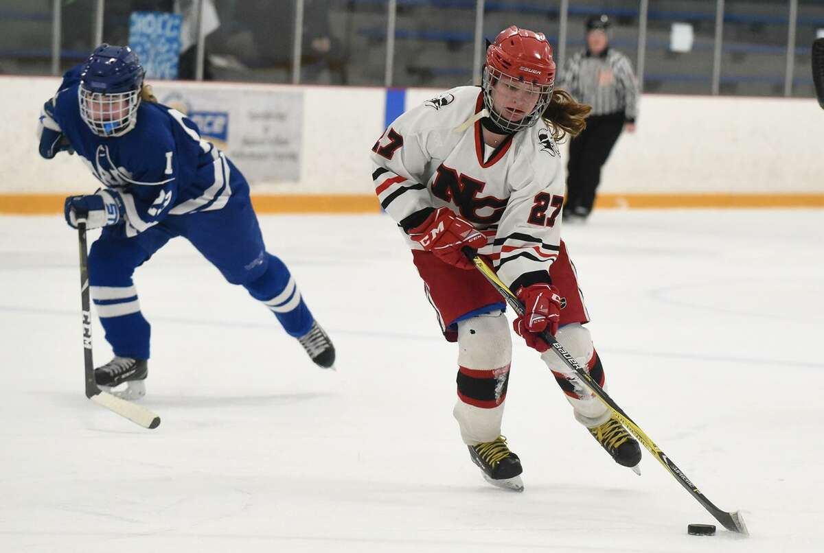 New Canaan's Maddie Kloud (27) lines up for a shot as Darien's Claire Haupt (1) pursues during the CHSGHA state final at Bennett Rink in West Haven on Saturday.