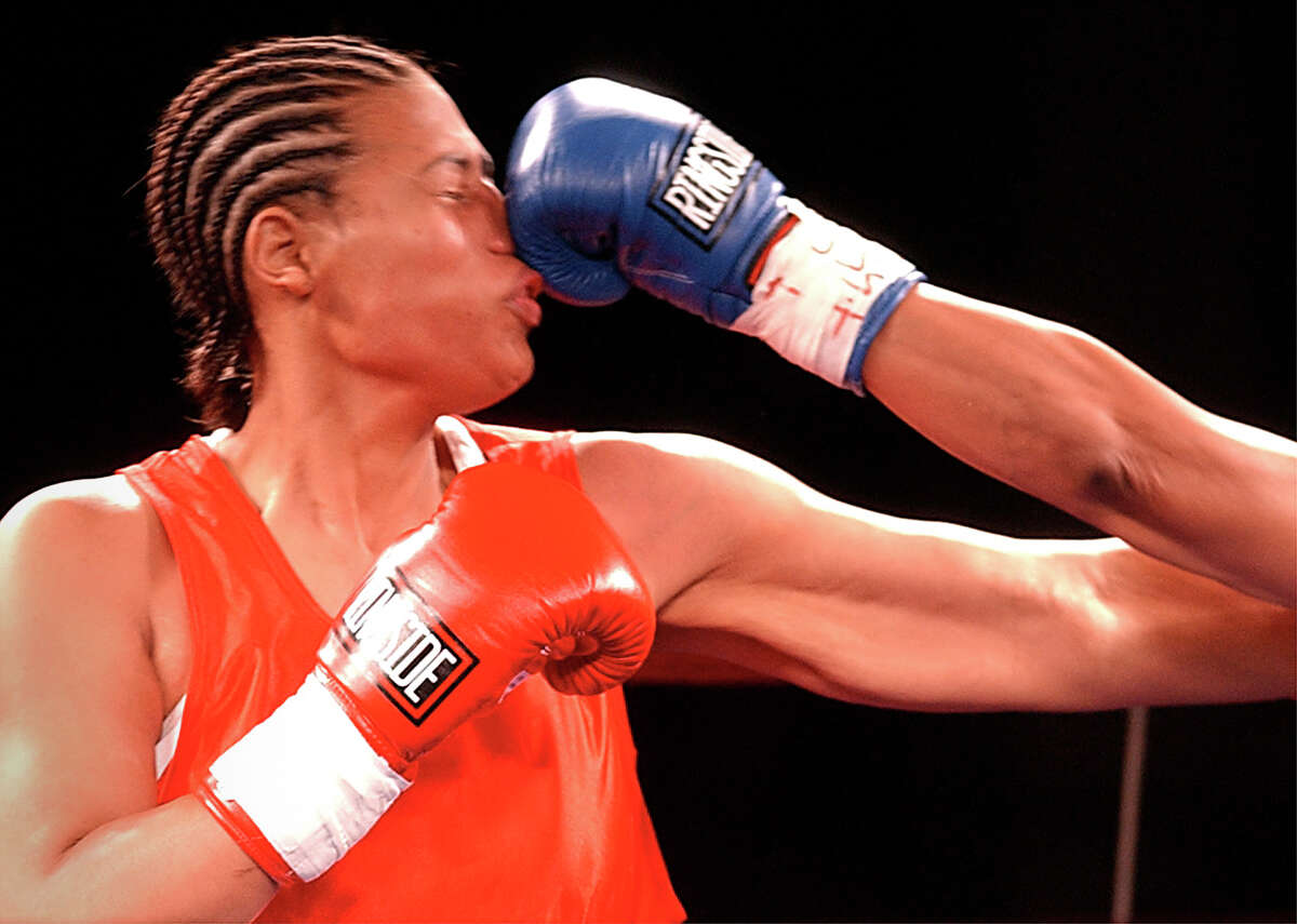 Freeda George Foreman, of Houston, takes a shot on the nose during her bout with Evelyn Rodriguez, of New York City, at the George Foreman All-Star Boxing Gala II at the Humble Civic Center in Humble, TX, Tuesday night, November 20, 2001. Foreman lost in a split decision.
