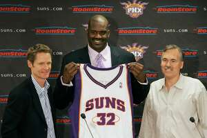 New Phoenix Suns' Shaquille O'Neal, center, holds up his new basketball jersey as he is flanked by Suns general manager Steve Kerr, left, and Suns head coach Mike D'Antoni at a news conference on Thursday, Feb. 7, 2008, in Phoenix. (AP Photo/Ross D. Franklin)