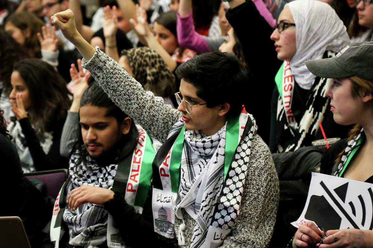 FILE - In this Tuesday, Nov. 14, 2017 file photo, a student holds up their fist in support of a speaker during a University of Michigan Student Government meeting in Ann Arbor, Mich., to vote on a resolution to divest in businesses connected to Israel amid criticism of Israeli policies toward Palestinians. On college campuses, in state legislatures and in many other venues nationwide, the polarized debate about Israel is a familiar conflict and likely to intensify. (Hunter Dyke/The Ann Arbor News via AP)