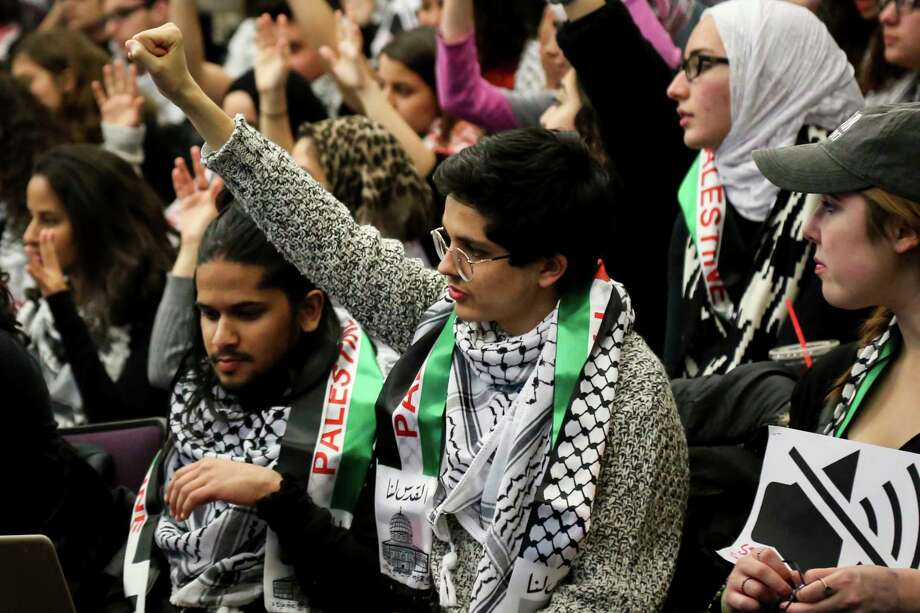 FILE - In this Tuesday, Nov. 14, 2017 file photo, a student holds up their fist in support of a speaker during a University of Michigan Student Government meeting in Ann Arbor, Mich., to vote on a resolution to divest in businesses connected to Israel amid criticism of Israeli policies toward Palestinians. On college campuses, in state legislatures and in many other venues nationwide, the polarized debate about Israel is a familiar conflict and likely to intensify. (Hunter Dyke/The Ann Arbor News via AP) Photo: Hunter Dyke / The Ann Arbor News