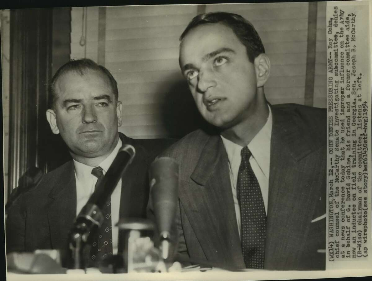 Roy Cohn, chief counsel of the McCarthy Senate Investigating subcommittee, denies at a news conference today that he used improper influence on the Army in behalf of G. David Schine, his friend and a former committee aide, now an inductee on field training in Georgia. Senator Joseph R. McCarthy, Republic, Wise, chairman of the committee, listens at left.