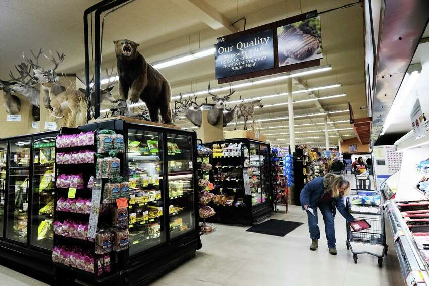 Dozens of taxidermied big game animals look down on shoppers at Hank's Harvest grocery store in Twisp, March 3, 2019. The animals were all killed by store owner Hank Konrad, many on trips to Africa or Canada. The animals, which include two lions, are prominently displayed in the store.