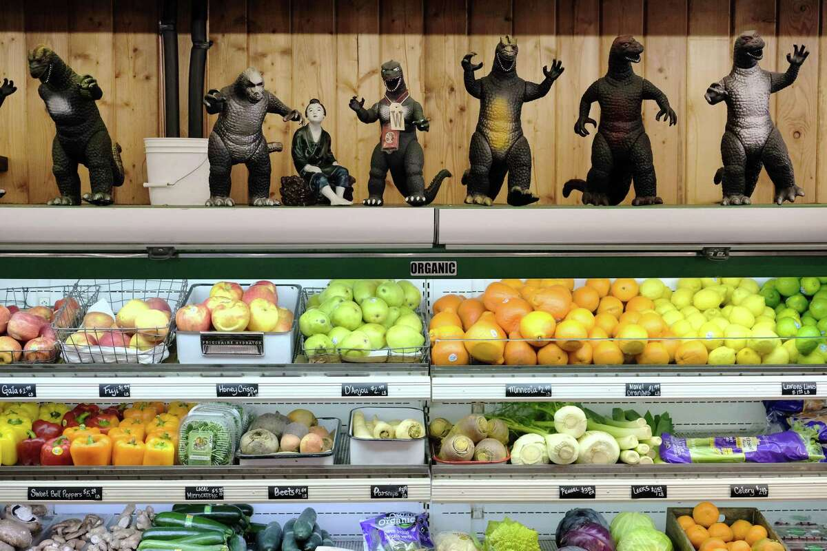 Toy Godzilla figurines keep watch over the produce aisle inside Twisp's Glover Street Market, a delightful grocery store that features a fresh, local food cafe, a juice bar and a downstairs wine cellar that offers tastings of both wines and olive oils.