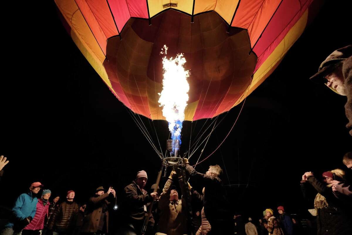 Kurt Oakley, center, who owns Morning Glory Balloons with his wife Melinda, sits in a