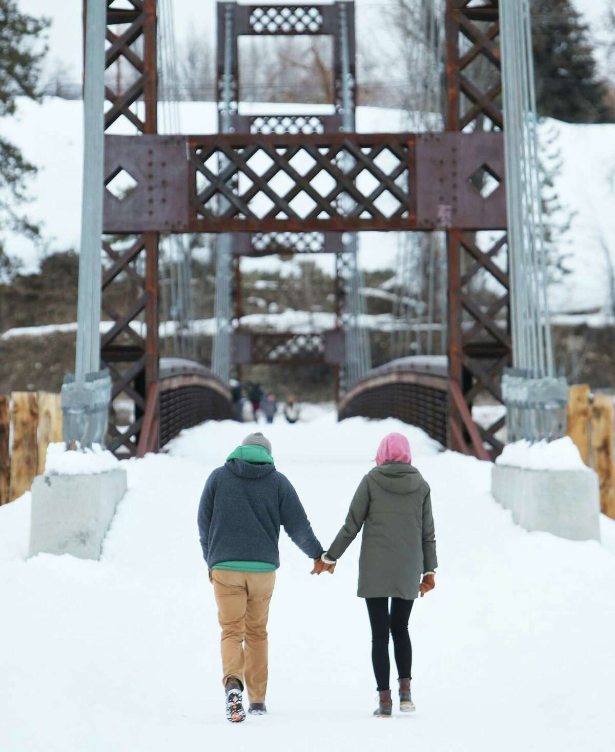 A couple walks over a snow-covered pedestrian bridge in Winthrop, March 2, 2019.
