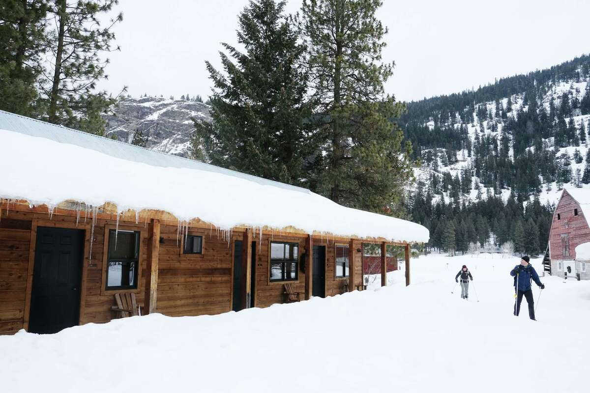 Cross-country skiers ski past the Mazama Ranch House which is next to the Mazama General Store and miles of groomed trails.