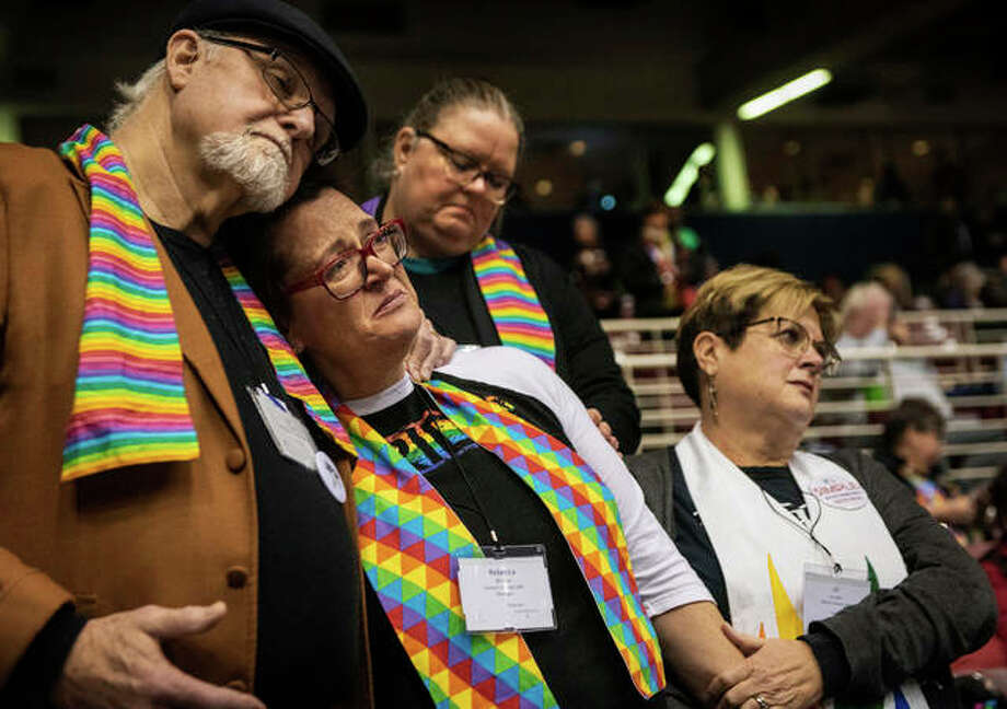 Ed Rowe, left, Rebecca Wilson, Robin Hager and Jill Zundel, react to the defeat of a proposal that would allow LGBT clergy and same-sex marriage within the United Methodist Church at the denomination's 2019 Special Session of the General Conference in St. Louis, Mo., Tuesday, Feb. 26, 2019. America's second-largest Protestant denomination faces a likely fracture as delegates at the crucial meeting move to strengthen bans on same-sex marriage and ordination of LGBT clergy. (AP Photo/Sid Hastings)