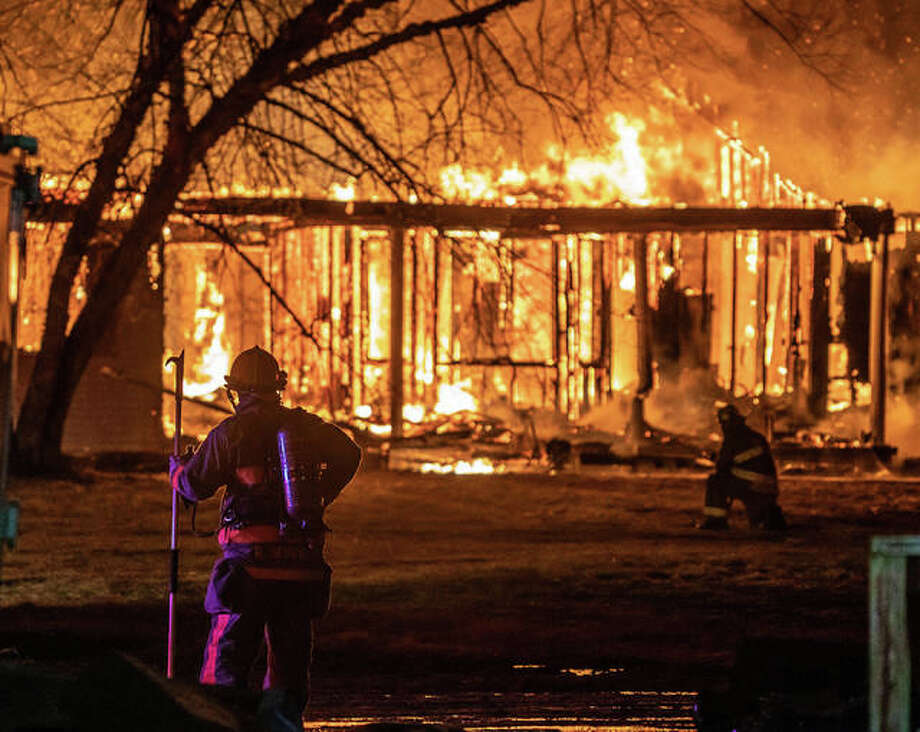 Firefighters look on as a home on Rocky Branch Road in rural Dorsey Saturday night. With little water supply, several tenders desperately rotated in and out for hours to keep flames from spreading to nearby horse stables. Photo: Nathan Woodside | The Telegraph