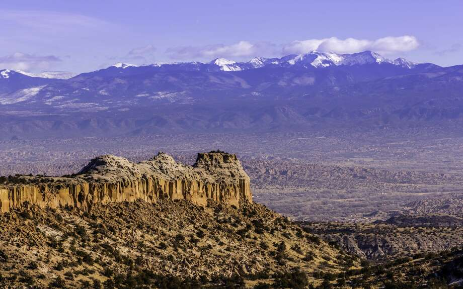 Rock formations and the snow-capped Rocky Mountains as seen from Los Alamos, New Mexico. Photo: Mabry Campbell/Getty Images