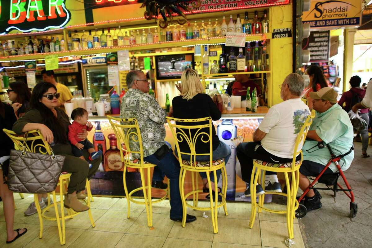 People enjoy drinks at a sidewalk bar in Nuevo Progreso, Mexico, on Saturday, Feb. 23, 2019. Years of drug cartel violence has all but killed jaunts across the Rio Grande to Mexican border cities like Matamoros and Reynosa, but Nuevo Progreso has somehow remained an oasis. It is as vibrant and busy as ever, with shop owners expanding square footage, street vendors doing a brisk trade, and long lines of beauticians offering bargain manicures and pedicures. Winter Texans make up a large part of the clientele, in part because they can cheaply fill prescriptions, take care of dental work, and imbibe generously of mixed margaritas.