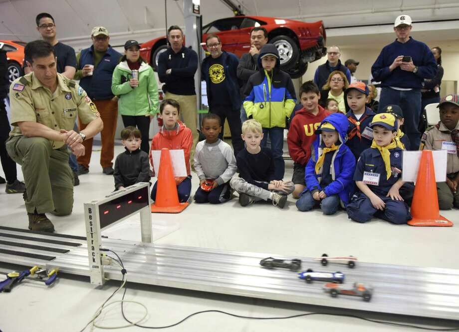 Scouts and parents gather to watch the Greenwich Boy Scouts Pinewood Derby Championship at Miller Motorcars in Greenwich, Conn. Sunday, March 10, 2019. Scouts built their cars by hand according to specific guidelines either at home or during the Pinewood Derby workshop in January. Local troops nominated their top three racers to compete in Sunday's championship, which featured 20 competitors. Cars' times were digitally tracked in multiple heats, allowing the fastest cars to advance to a bracket of eight and then the final championship round of four. Colby Loflin, of Old Greenwich Cub Scout Pack 3, won first place overall and Galen Hsu, of North Mianus Cub Scout Pack 23, won Best in Show for his car design. Photo: Tyler Sizemore / Hearst Connecticut Media / Greenwich Time
