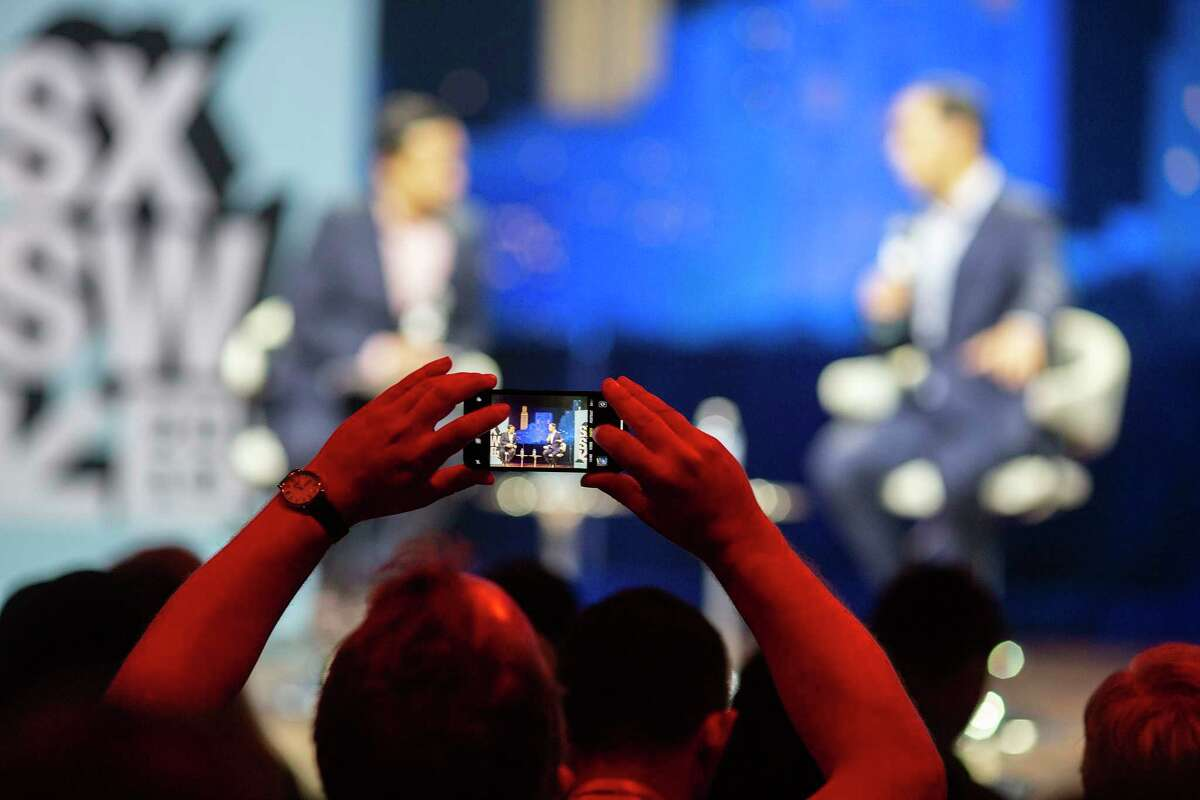 A SXSW fest goer takes a photo on his cell phone of former U.S. Secretary of Housing and Urban Development, Julian Castro, which he chats with moderator Lydia Polgreen, the editor of HuffPost during a Conversation About America's Future session during SXSW on March 10, 2019 in Austin, Texas.