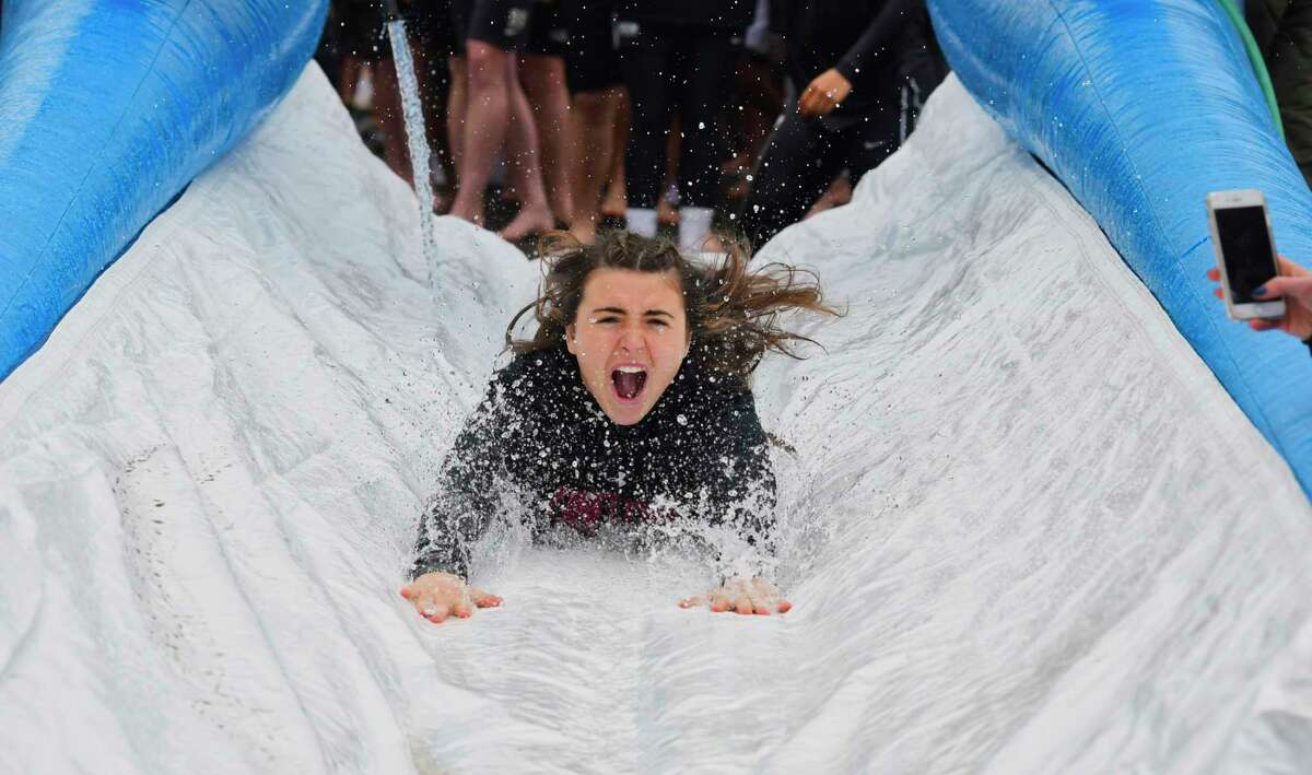 A Union College women's lacrosse player heads down the water slide during the 7th annual Dutchmen Dip event on Sunday, March 10, 2019, in Schenectady, N.Y. The event, put on by the Colleges Against Cancer club, had been held to raise money for members of the Union community currently battling cancer. The funds directly supported each year's honorees helping to cover costly medical treatments. This year's Dip was held in memory of Kristen Shinebarger who passed away last year at the age of 16. Kristen inspired the first Dutchmen Dip in 2013. All proceeds from this year's Dip will support the Shinebarger Memorial Scholarship at Union College. Union Senior, Sophie Rosen, who has been the club president the past three years, said that the scholarship going forward would be awarded each year to a student who exhibits the qualities Kristen had and they show real courage, determination, and grace in the face of personal hardship. (Paul Buckowski/Times Union)