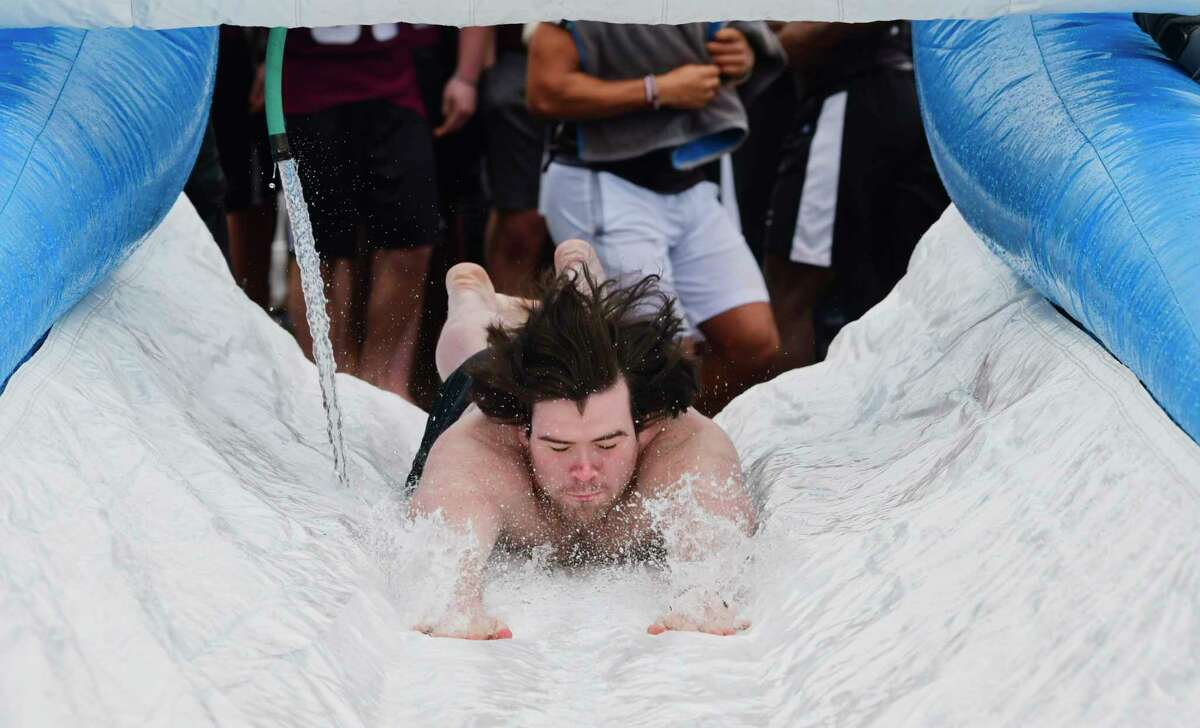 A Union College student heads down the slide during the 7th annual Dutchmen Dip event on Sunday, March 10, 2019, in Schenectady, N.Y. The event, put on by the Colleges Against Cancer club, had been held to raise money for members of the Union community currently battling cancer. The funds directly supported each year's honorees helping to cover costly medical treatments. This year's Dip was held in memory of Kristen Shinebarger who passed away last year at the age of 16. Kristen inspired the first Dutchmen Dip in 2013. All proceeds from this year's Dip will support the Shinebarger Memorial Scholarship at Union College. Union Senior, Sophie Rosen, who has been the club president the past three years, said that the scholarship going forward would be awarded each year to a student who exhibits the qualities Kristen had and they show real courage, determination, and grace in the face of personal hardship. (Paul Buckowski/Times Union)