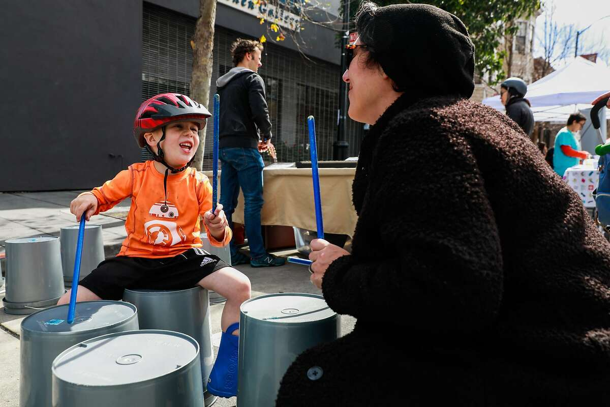Maxwell Peters,4 looked up at his mother Genny May-Montt as they played drums on buckets during Sunday Streets where Valencia Street was car-free and open for the public to enjoy in San Francisco, California, on Sunday, March 10, 2019.