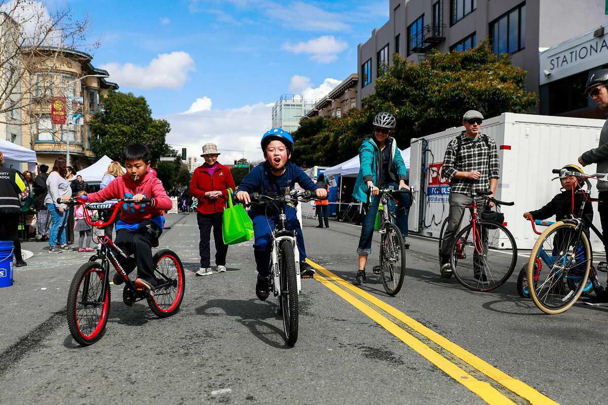 Jordan Hong, 8 (left) and Guus Vroegh, 8 (center) ride their bikes with friends during Sunday Streets where Valencia Street was car-free and open for the public to enjoy in San Francisco, California, on Sunday, March 10, 2019.