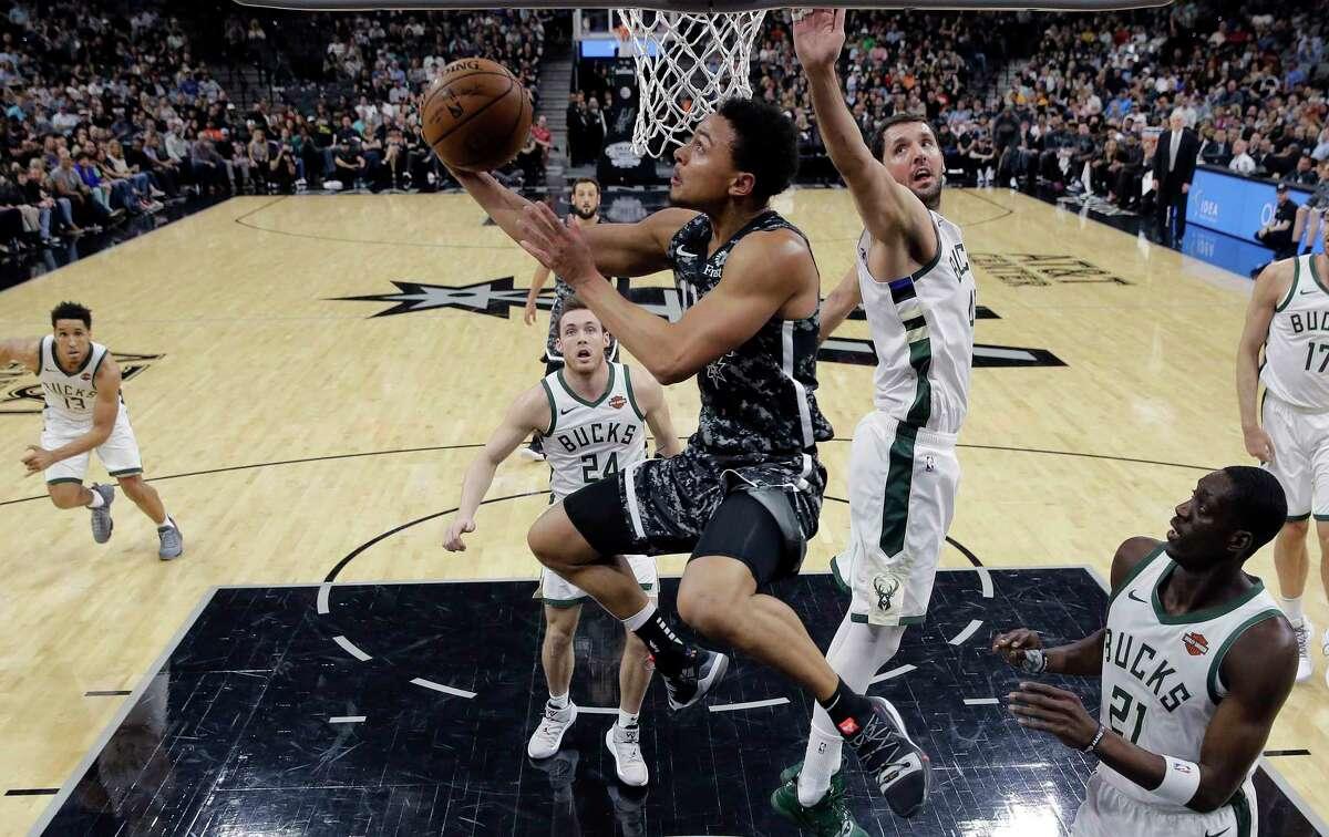 San Antonio Spurs guard Bryn Forbes (11) drives to the basket past Milwaukee Bucks forward Nikola Mirotic (41) during the first half of an NBA basketball game, in San Antonio, Sunday, March 10, 2019. (AP Photo/Eric Gay)