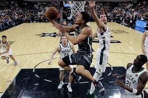 San Antonio Spurs guard Bryn Forbes (11) drives to the basket past Milwaukee Bucks forward Nikola Mirotic (41) during the first half of an NBA basketball game, in San Antonio, Sunday, March 10, 2019. (AP Photo/Eric Gay)