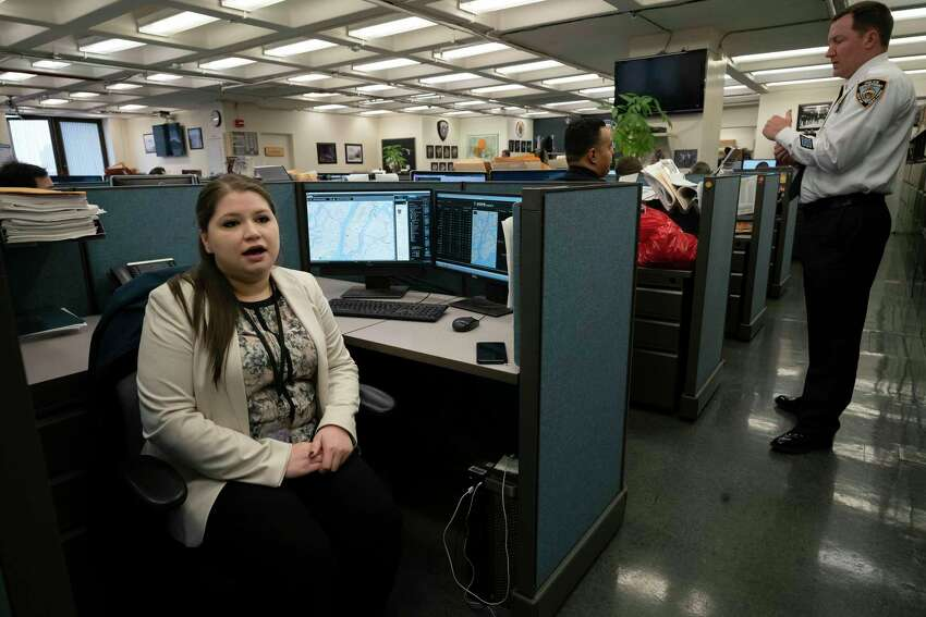 In this Feb. 11, 2019 photo, Rebecca Shutt, left, who works in the New York Police Department's Office of Crime Control Strategies, speaks in New York. Shutt utilizes a software called Patternizr, which allows crime analysts to compare robbery, larceny and theft incidents to the millions of crimes logged in the NYPD's database, aiding their hunt for crime patterns. It's much faster than the old method, which involved analysts sifting through reports and racking their brains for similar incidents. (AP Photo/Mark Lennihan)
