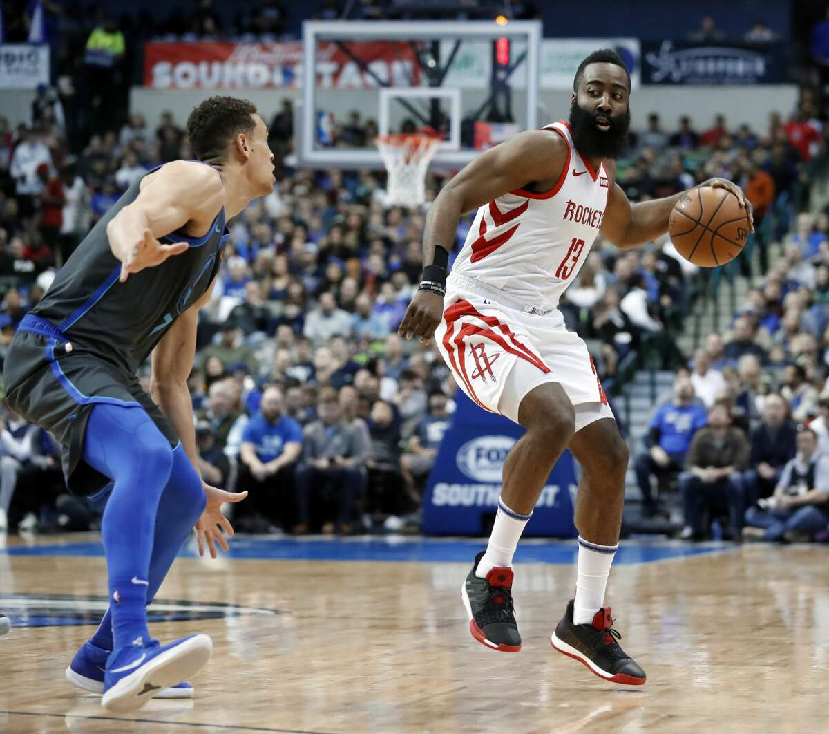 Dallas Mavericks' Dwight Powell, left, defends as Houston Rockets guard James Harden (13) handles the ball in the first half of an NBA basketball game in Dallas, Sunday, March 10, 2019. (AP Photo/Tony Gutierrez)