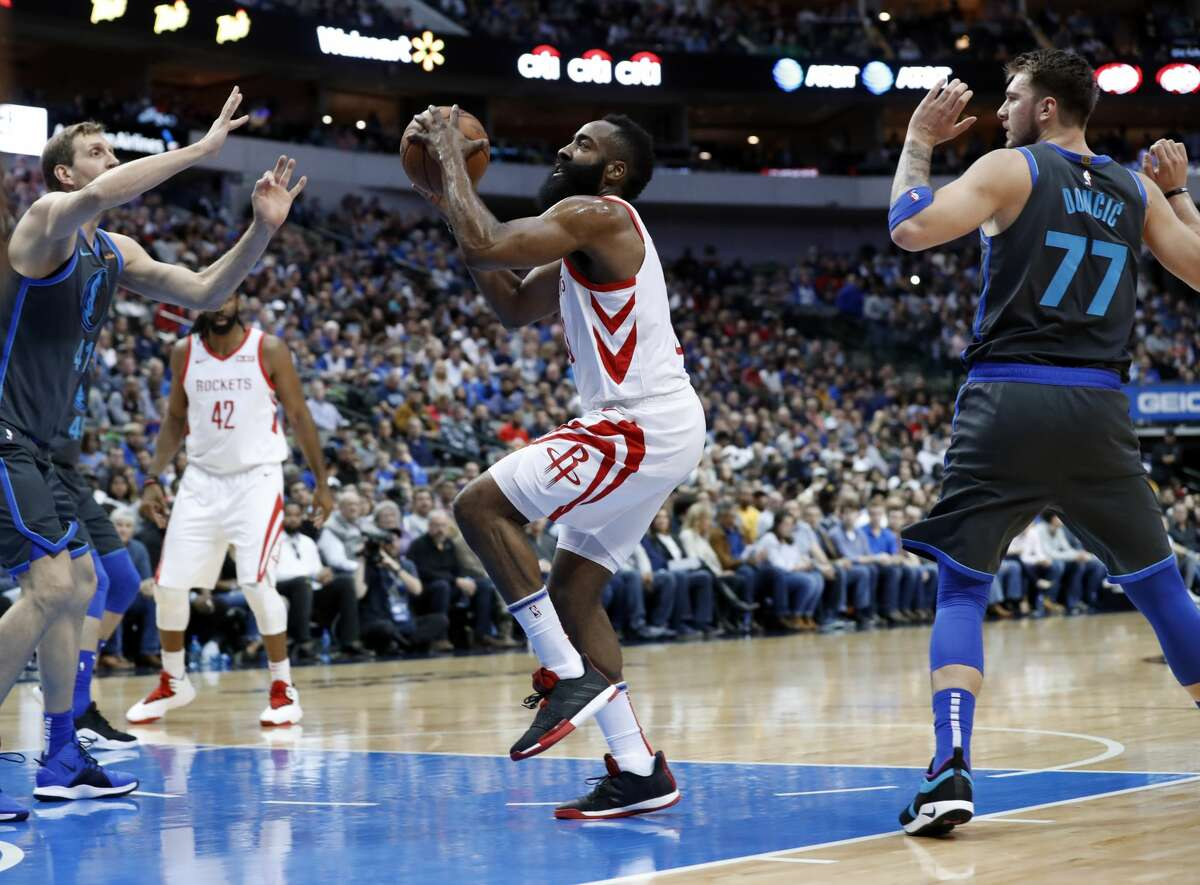 Dallas Mavericks' Dirk Nowitzki, left, and Luka Doncic (77) defend as Houston Rockets guard James Harden (13) drives to the basket in the first half of an NBA basketball game in Dallas, Sunday, March 10, 2019. (AP Photo/Tony Gutierrez)
