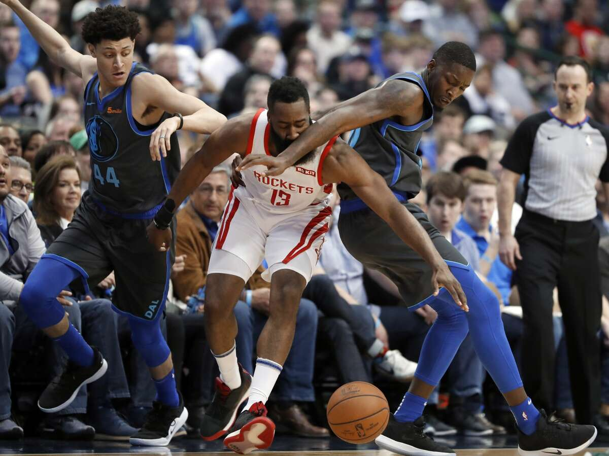 Houston Rockets guard James Harden (13) works against Dallas Mavericks forward Justin Jackson (44) and Dorian Finney-Smith (10) for control of a loose ball in the second half of an NBA basketball game in Dallas, Sunday, March 10, 2019. (AP Photo/Tony Gutierrez)