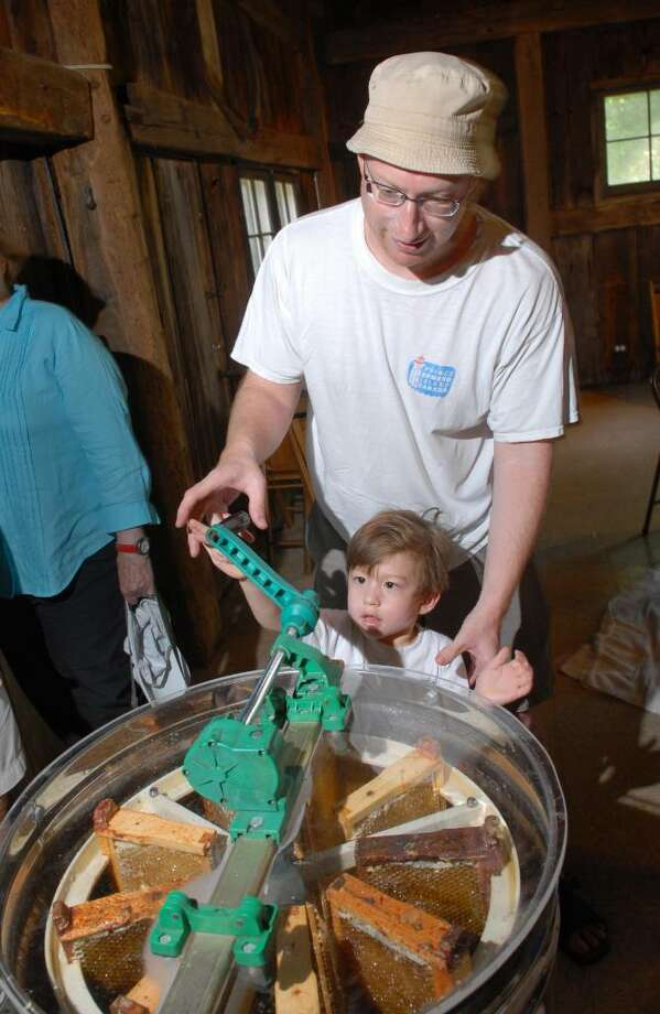 Julian Boesch, 3, of Cos Cob, turns the crank on the honey extractor with assistance from his father Joe, during Honey Bee Day at Audubon Greenwich, Saturday morning, July 24, 2010. Photo: Bob Luckey / Greenwich Time